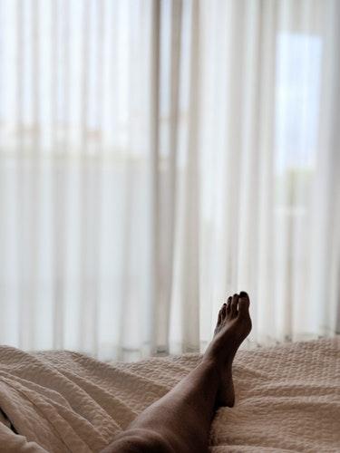 Femme couchée dans un lit dont on ne voit que le pied