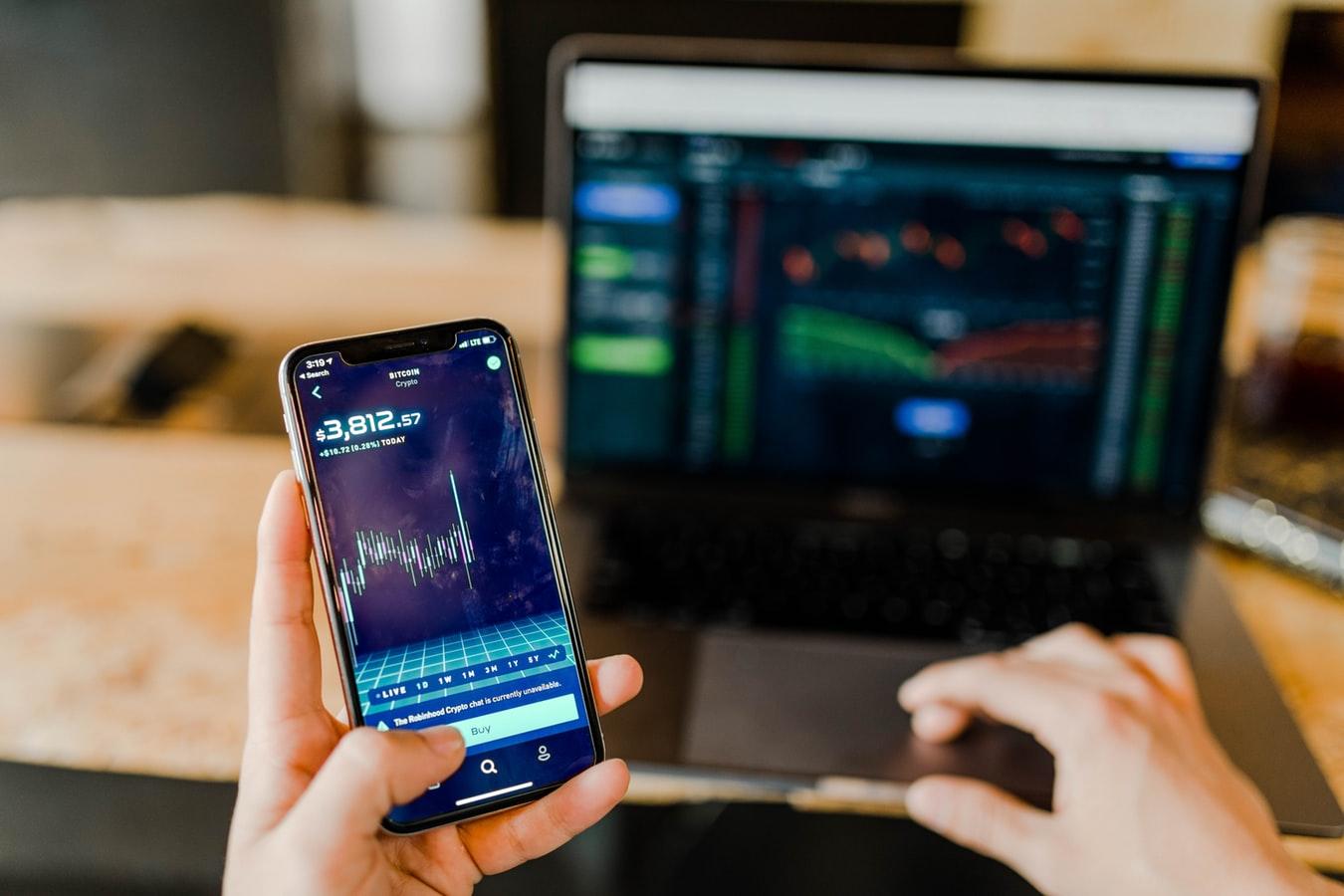 Un homme manipulant son téléphone et l'ordinateur sur lesquels s'affiche des diagrammes à propos du Bitcoin