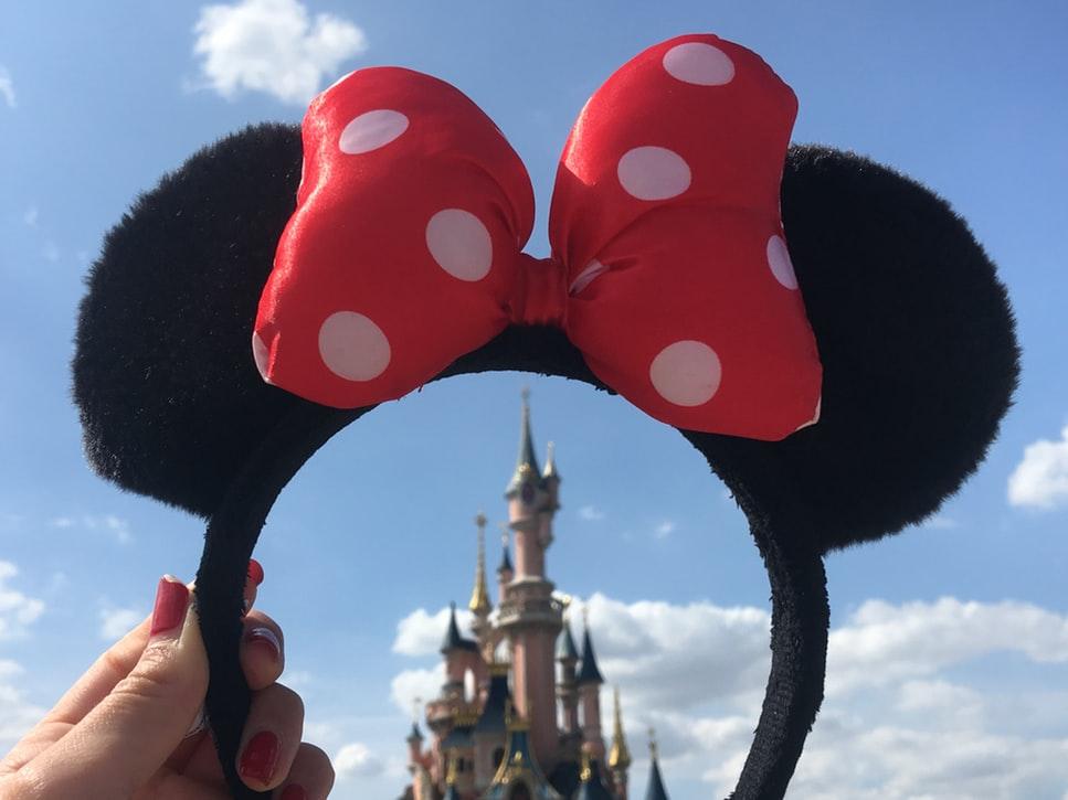 Une personne tenant a couronne de Minnie Mouse au-dessus de la tour de Disneyland Paris.