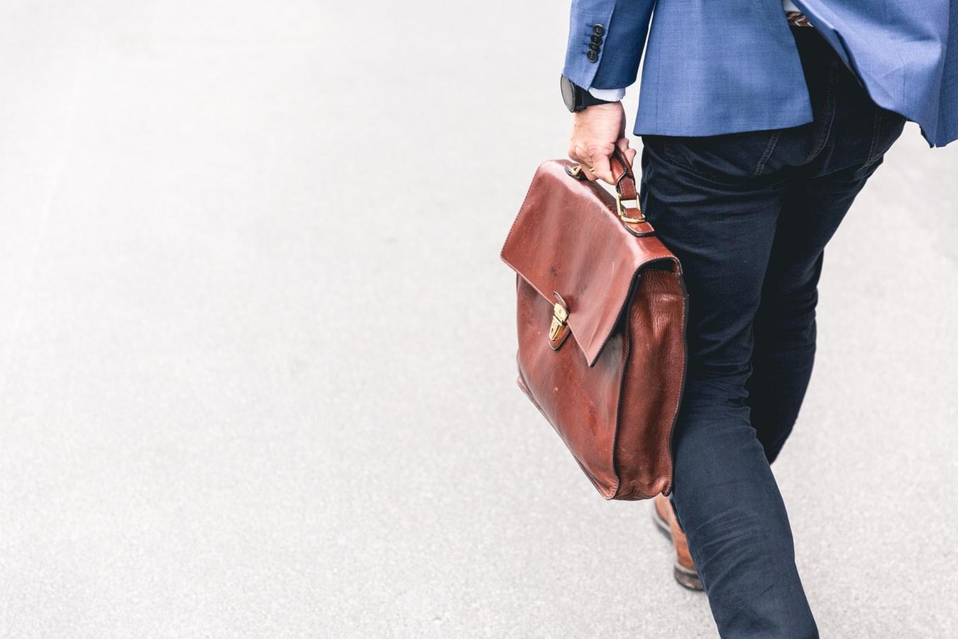 Un homme en route pour le travail avec un sac en main.