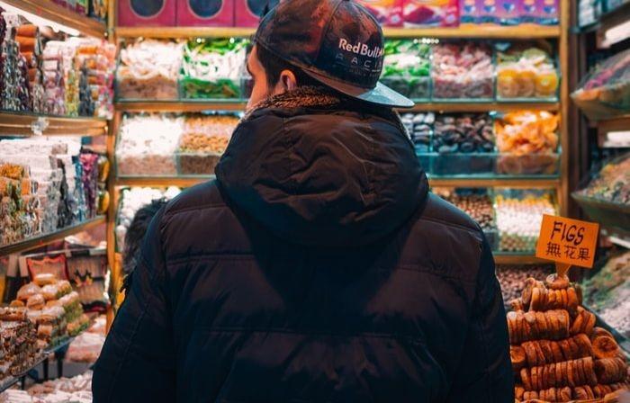 Un homme vu de dos, arrêté devant un rayon dans un magasin.