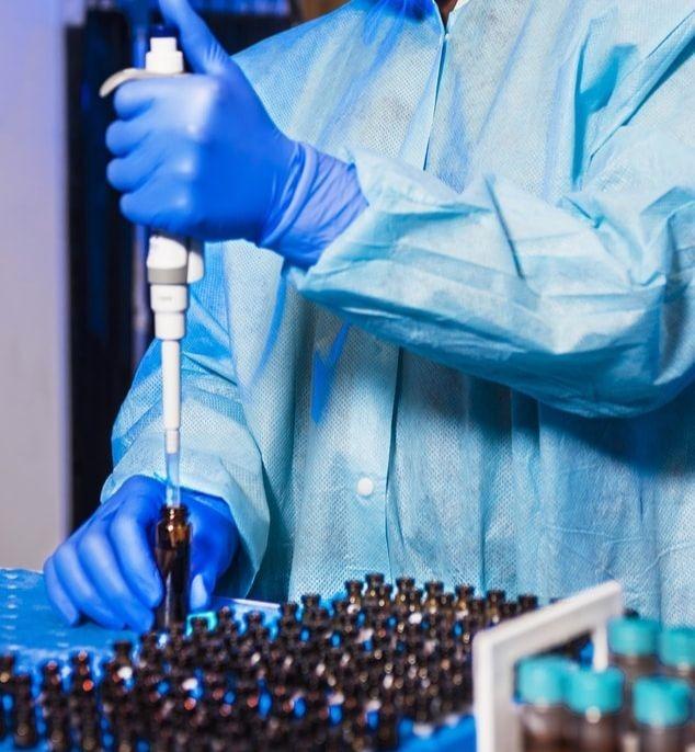 Une chercheuse piquant une séringue dans un patch de vaccin.
