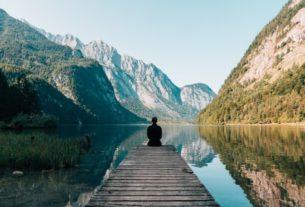 Un homme en pleine méditation près d'un lac.