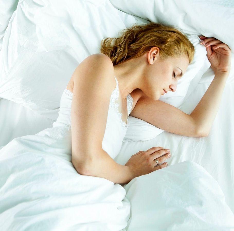Une femme endormie sur son lit.