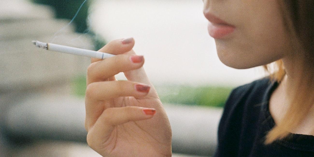 Une jeune fille fumant une cigarette.